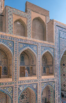 Female traveler walking on terrace of arched Islamic building with blue ornaments while visiting Registan in Samarkand, Uzbekistan - ADSF15273
