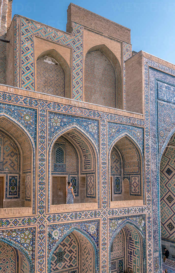 Female traveler walking on terrace of arched Islamic building with blue ornaments while visiting Registan in Samarkand, Uzbekistan - ADSF15273 - ADDICTIVE STOCK CREATIVES/Westend61