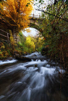 Majestic scenery of river flowing through forest and under bridge in long exposure in Granada - ADSF15306