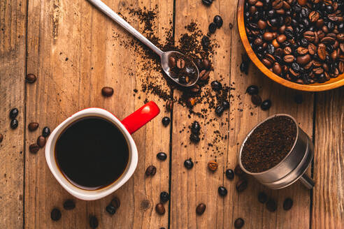 Top view of delicious beverage in mug placed on table with coffee beans and ground coffee in metal filter - ADSF15309