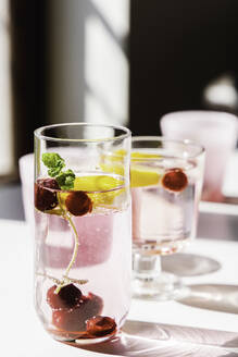 Fresh detox water with cherry and mint placed on table lit by sun in modern apartment - ADSF15318