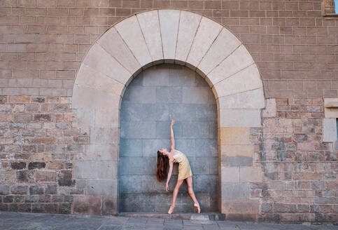 Full body of graceful young female dancer standing in ballet pose against weathered brick wall with arched ornament - ADSF15327