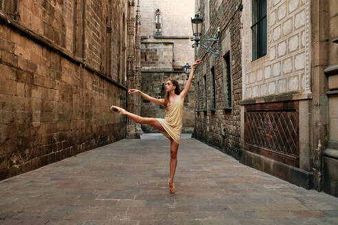 Full body of talented young female ballet dancer in dress and pointe shoes performing dance movement with leg outstretched on narrow paved passage between old stone buildings - ADSF15330