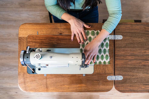From above unrecognizable craftswoman using modern sewing machine while creating soft fabric samples with creative green pattern near lamp in loft style workshop - ADSF15363