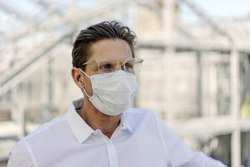 Close-up of businessman wearing face mask looking away in greenhouse - JOSEF01638
