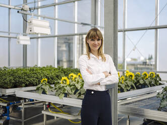 Confident businesswoman with arms crossed standing against plants in greenhouse - JOSEF01641