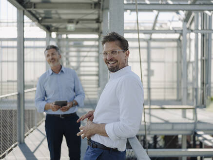Smiling businessman standing with male coworker on footbridge in greenhouse - JOSEF01692