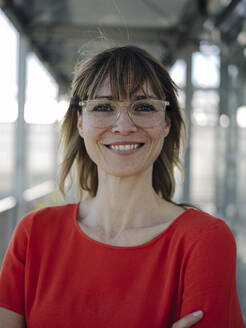 Close-up of smiling businesswoman wearing eyeglasses in greenhouse - JOSEF01701