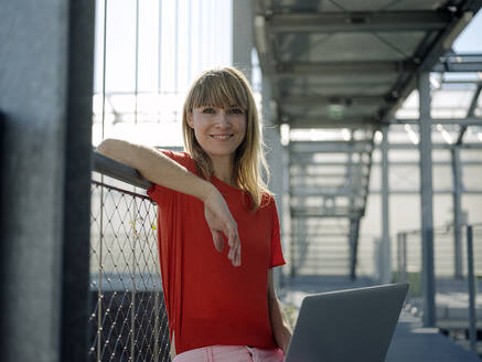 Smiling businesswoman using laptop while sitting by railing in greenhouse - JOSEF01704