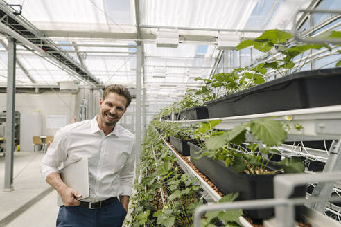 Smiling male owner with laptop standing by plants in greenhouse - JOSEF01728