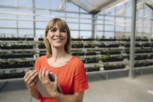Smiling female entrepreneur holding digital tablet looking away in plant nursery - JOSEF01770