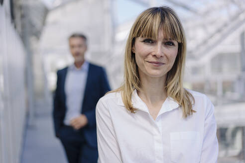 Close-up of smiling businesswoman with male coworker in background at greenhouse - JOSEF01821