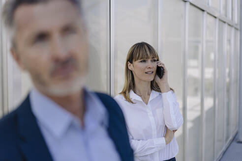 Female professional talking over smart phone against wall in greenhouse - JOSEF01827