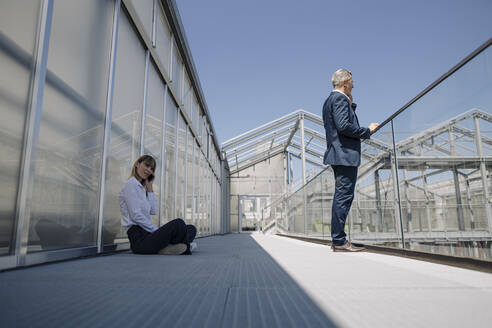 Male and female coworkers talking over smart phone on footbridge in greenhouse - JOSEF01836