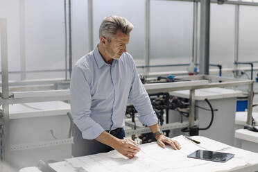 Businessman analyzing blueprint on table in greenhouse - JOSEF01863