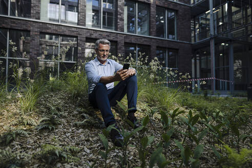 Businessman using smart phone while sitting amidst plants against building - JOSEF01884
