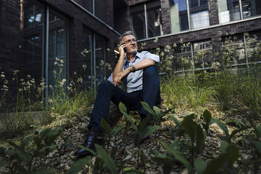Businessman talking over smart phone while sitting amidst plants against building - JOSEF01887