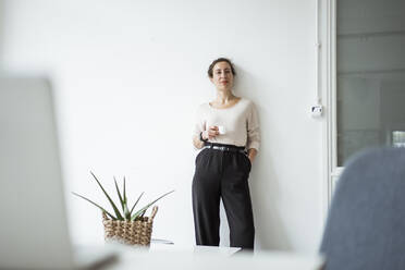 Confident businesswoman with hand in pocket holding coffee cup while standing against white wall - JOSEF01910
