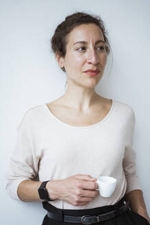 Thoughtful female entrepreneur holding coffee cup standing against white wall - JOSEF01913