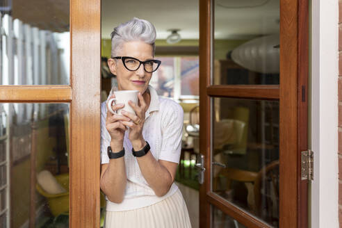 Senior woman leaning on doorway while holding coffee cup at home - WPEF03332