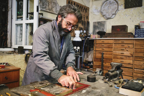 Craftsman cleaning etching with creative ornament in golden frame using hard piece of fabric in workshop - ADSF15433