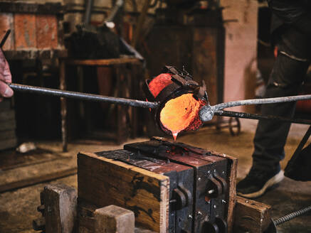 Crop of group of professional male artisans working in weathered workshop and pouring molten metal into mold cavity during metal casting process - ADSF15445