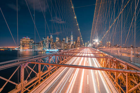 Empty roadway of illuminated Brooklyn bridge at night time with glowing skyscrapers in background in New York City - ADSF15502