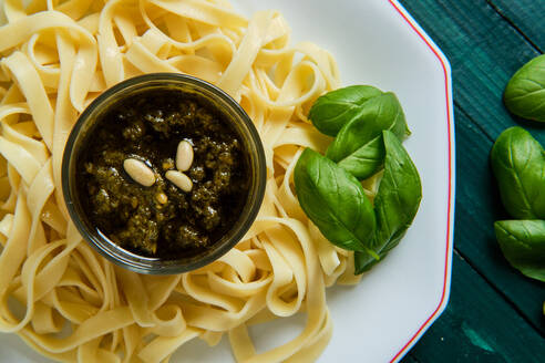 From above of yummy tagliatelle with Italian pesto sauce on top decorated with crunchy pine nuts and fresh basil leaves - ADSF15662