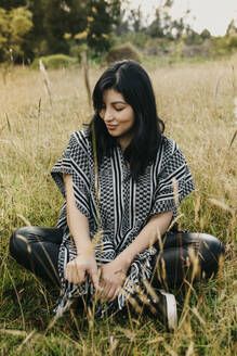 Beautiful woman looking down at grass while sitting in public park - DSIF00108
