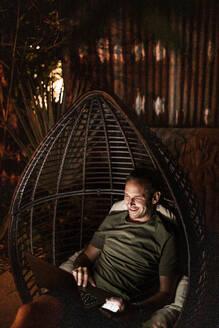 Smiling man using laptop while sitting in hanging chair at night - MASF19627