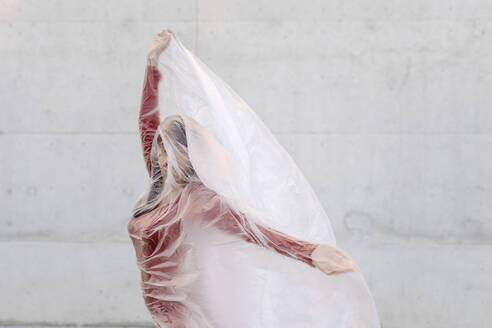 Young woman doing hand gesture while wrapped inside plastic - TCEF01052