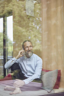 Bearded mature man talking over smart phone while sitting on bed in tiny house seen through window - MCF01383