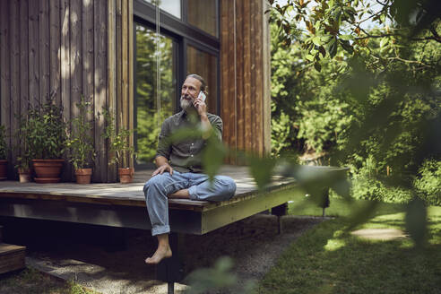 Mature man looking away while talking over mobile phone outside tiny house - MCF01467