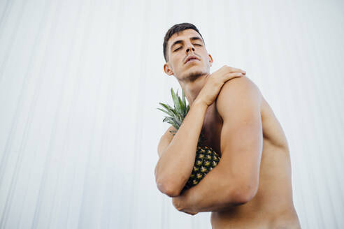 Man hugging pineapple while standing against wall - MIMFF00209