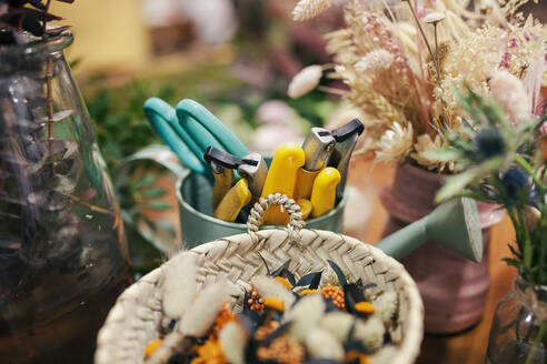 Gardening tool and flowers kept on table at flower shop - MRRF00393