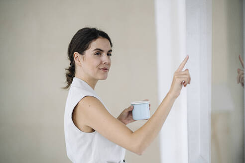 Businesswoman pointing at glass wall while standing at office - KNSF08429