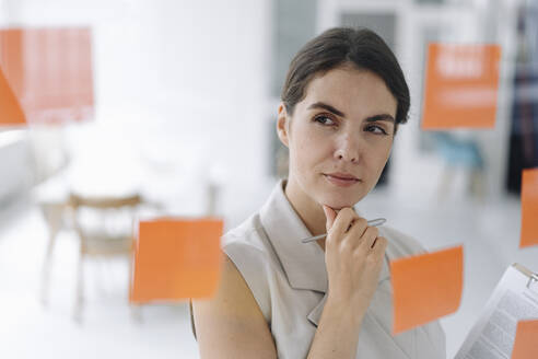Thoughtful businesswoman standing with hand on chin at office - KNSF08435