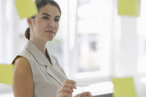 Businesswoman holding pen while working at office - KNSF08444