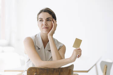 Young woman holding business card while sitting on chair at office - KNSF08459