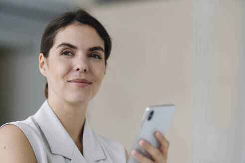 Smiling woman holding mobile phone while standing at office - KNSF08465