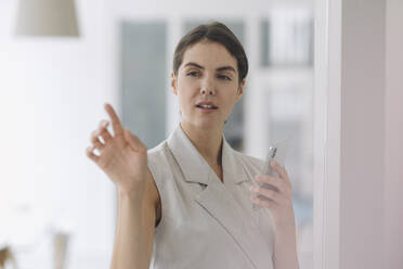 Young woman pointing at glass wall while using mobile phone at office - KNSF08471