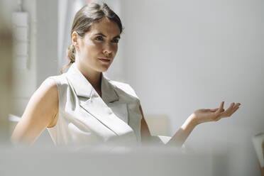 Young woman gesturing while sitting on chair at office - KNSF08483