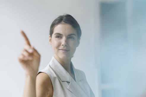 Smiling woman pointing on glass wall while standing at office - KNSF08492