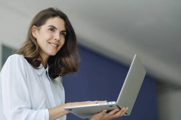 Businesswoman holding laptop while standing at office - KNSF08498
