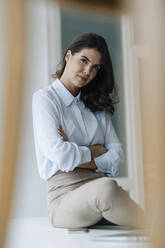 Businesswoman with arms crossed sitting on floor at office - KNSF08501