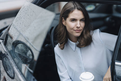 Young woman holding coffee cup while sitting in car - KNSF08519