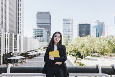 Confident businesswoman with book standing against downtown district in city - MRRF00435