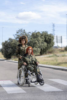 Army soldier helping disabled military officer on wheelchair while standing on street - OCMF01666