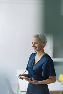 Smiling female entrepreneur with digital tablet looking away while standing in office - KNSF08577