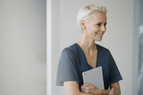 Smiling businesswoman holding digital tablet looking away while standing against wall in office - KNSF08589